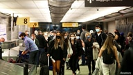 US Travelers wearing protective face masks to prevent the spread of the coronavirus disease (COVID-19) reclaim luggage.