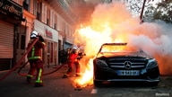 "Firefighters extinguish cars on fire during a demonstration against the ""Global Security Bill"" that rights groups say would…"