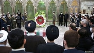 Mourners and members of Iranian forces stand around the coffin of Iranian nuclear scientist Mohsen Fakhrizadeh at the Imam…