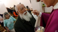 FILE - A priest gives communion host during a mass in a convent of Saint Germain en Laye, west of Paris.