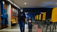 Lisa Carrera, a former Los Angeles Unified School history teacher from La Puente, Calif., holds the hand of her grandson.