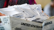 A election worker moves a tray of ballots as vote counting in the general election continues at State Farm Arena on Thursday,…