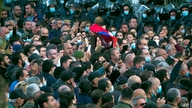 Protesters gather near the parliamentary building during a protest against an agreement to halt fighting over the Nagorno…