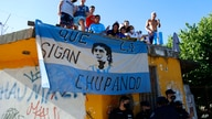 Fans stand on a roof of a house along the way of the motorcade carrying the remains of Diego Maradona to the Jardin de…