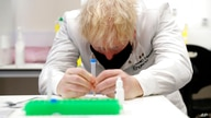 Britain's Prime Minister Boris Johnson, wearing a mask because of the coronavirus,  has a close look at a sample at the Lateral…