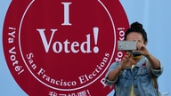 A woman takes a photo in front of an I Voted sign at a San Francisco Department of Elections voting center in San Francisco,…