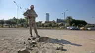 A member of the Iraqi security forces inspects the damage outside the Zawraa park in the capital Baghdad, Nov. 18, 2020, after volley of rockets slammed into the Iraqi capital breaking a month-long truce on attacks against the U.S. embassy.