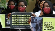 FILE - Protesters wearing face mask hold placards outside the Nigerian Police Headquarters in Abuja, Nigeria, during a rally to raise awareness about sexual violence in Nigeria, June 5, 2020.