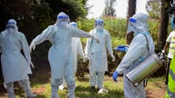 FILE - Health workers wearing protective suits prepare to bury coronavirus victim Dr. Doreen Adisa Lugaliki, at her funeral in Ndalu, Bungoma county, Kenya, July 13, 2020.