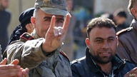 A man wearing a Turkish officer's uniform flashes the Grey Wolves (a Turkish far-right ultranationalist organization) sign,…