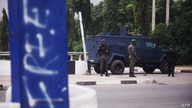 Policemen guard the road to the Aso Villa, official residence of the President of Nigeria, during clashes between members of…