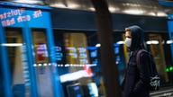 A commuter wearing a protective face mask waits for the metro at Stockholm's central station on December 3, 2020, during the…