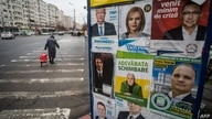 People pass by an electoral billboard displaying various candidates for the incoming parliamentary elections in Bucharest on…
