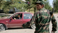 A serviceman stands guard at a road block outside Dushanbe, September 24, 2010. Tajik troops killed three Islamist militants on…