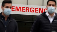 People walk past a hospital Emergency room sign during the coronavirus (COVID-19) pandemic in the Manhattan borough of New York…