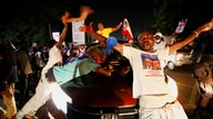 Supporters of Ghana's President Nana Akufo-Addo celebrate outside his residence as he is declared winner of the presidential…