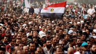 FILE PHOTO: A man holds an Egyptian flag during a rally at Tahrir Square, in Cairo February 25, 2011. Egypt's new military…