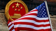 FILE - In this Nov. 9, 2017, file photo, an American flag is flown next to the Chinese national emblem during a welcome…
