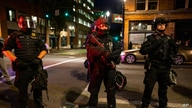 FILE - In this Aug. 29, 2020, file photo, Portland police stand guard in Portland, Ore. Reporters — whether they're from major…