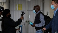 FILE - Passengers have their temperatures taken at the International O.R. Tambo Airport in Johannesburg, Oct. 1, 2020.