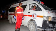 Medical workers wait by ambulances ready to transport wounded, after a bomb attack at an ice cream shop in Mogadishu, Somalia,…
