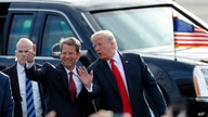FILE - Then-Georgia Republican gubernatorial candidate Brian Kemp, left, walks with President Trump