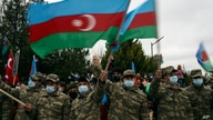 Azerbaijani soldiers wave national flags as they celebrate the transfer of the Lachin region to Azerbaijan's control, as part of a peace deal that required Armenian forces to cede the Azerbaijani territories they held outside Nagorno-Karabakh, Dec. 1, 2020.