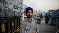 Farmer Harinder Singh, 28, stands for a photograph next to his tractor parked on a highway during a protest.