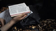 FILE - A woman holding a bible during a Christmas Eve service held by members of an underground church, at an apartment in Beijing, Dec. 24, 2014.