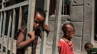 Children play in front of a bullet-ridden wall of a destroyed store in the village of Bisober, in Ethiopia's Tigray region, Dec. 9, 2020.