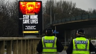 Police officers walk past a Covid-19 information board alongside the  Clydeside Expressway in Glasgow on January 20, 2021. …