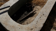 An unexploded rocket propelled grenade lies inside a cement water catchment in the village of Nialdhiu, northern South Sudan, Feb. 7, 2017.