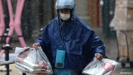 An Ele.me deliveryman wearing a face mask delivers food amid snowfall, following an outbreak of the novel coronavirus in the…