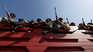 FILE PHOTO: Militia members from Ethiopia's Amhara region ride on their truck as they head to face the Tigray People's…