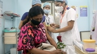 A healthcare worker holding a rose receives an AstraZeneca's COVISHIELD vaccine, during the coronavirus disease (COVID-19) vaccination campaign, at a medical centre in Mumbai, India, Jan. 16, 2021.