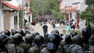 Guatemalan soldiers block a street as Honduran migrants gather after Guatemalan security forces cleared a road where they were…