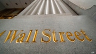 FILE - In this Nov. 5, 2020 file photo, a sign for Wall Street is carved in the side of a building.  U.S. stocks are rising…
