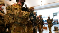 Troops stand in formation inside the Capitol Visitor's Center to reinforce security at the Capitol in Washington, Wednesday,…