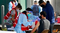 FILE - In this Jan. 13, 2021, file photo, health care workers receive a COVID-19 vaccination at Ritchie Valens Recreation…