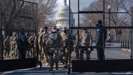 With the U.S. Capitol in the background, members of the National Guard change shifts as they exit through anti-scaling security…