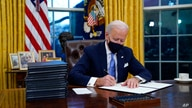 President Joe Biden signs his first executive order in the Oval Office of the White House on Wednesday, Jan. 20, 2021, in…