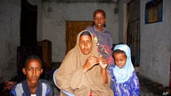 Fatuma Moallim Abdulle poses with 3 of her children, during an interview with the Associated Press in Mogadishu, Somalia,