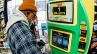 A patron, who did not want to give his name, uses the lottery ticket vending kiosk at a Smoker Friendly store to purchase…