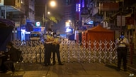 Police officers wearing masks, stand guard at the closed area in Jordan district, in Hong Kong, Sunday, Jan. 24, 2021…