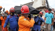 Rescuers carry the body of an earthquake victim retrieved from the ruin of a building damaged by an earthquake in Mamuju, West Sulawesi, Indonesia, Jan. 16, 2021.