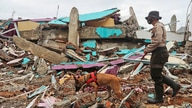 A police officer leads a sniffer dog during a search of victims at the ruin of a building flattened by an earthquake in Mamuju, West Sulawesi, Indonesia, Jan. 17, 2021.