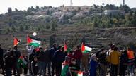 FILE - Palestinians protest against expected visit of the U.S. Secretary of State Mike Pompeo to the Jewish settlement of Psagot near the West Bank city of Al-Bireh, Nov. 18, 2020.