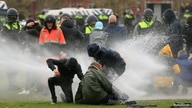 Police use a water canon during a protest against restrictions put in place to curb the spread of the coronavirus, in Amsterdam, Netherlands, Jan. 24, 2021.