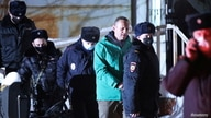 Russian opposition leader Alexei Navalny is escorted by police officers after a court hearing, in Khimki outside Moscow, Russia Jan. 18, 2021.