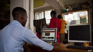 A man uses a computer to read news at a cyber cafe minutes after the Uganda Communication Commission, a body responsible for…